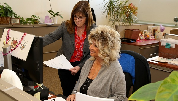 Volunteer Recruitment Coordinator Regina Mayo, seated, works with supervisor Pamela Sullivan.